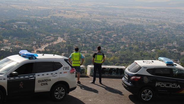 Un agente de la Guardia Civil y otro de la Policía Nacional en la carretera de acceso a Trassierra