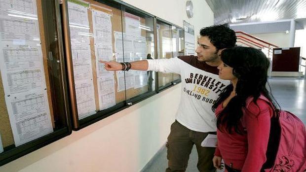 Unos jóvenes miran un tablón de anuncios de la UCO