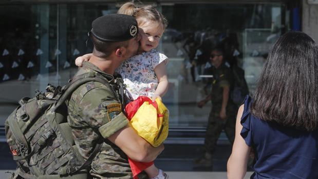 Un soldado con su hija en brazos en su retorno a casa