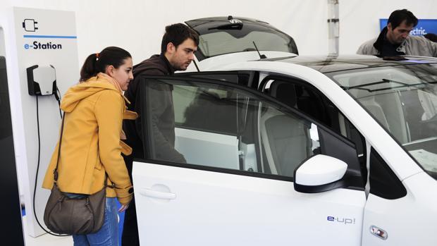 Dos personas observan en un concesionario un coche eléctrico, junto a un punto de recarga