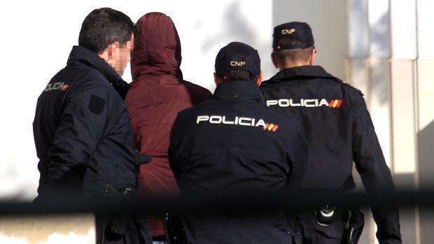 Tres policías llevan al joven acusado de violación ante el juez