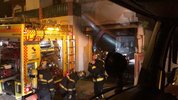 Tres efectivos del Consorcio de Bomberos, ante el garaje donde se ha producido el incendio