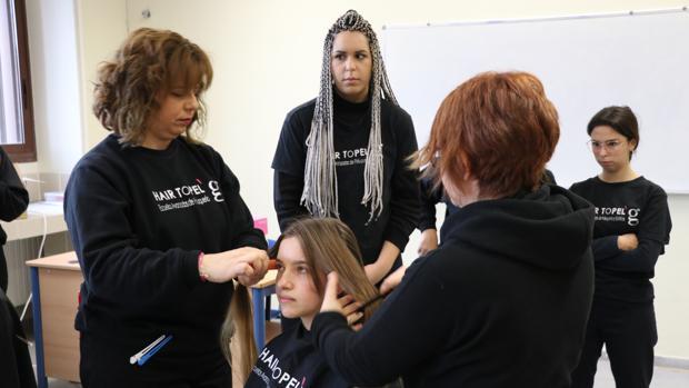 Empleados de una peluquería cortan el pelo de los jóvenes que quieran donarlo