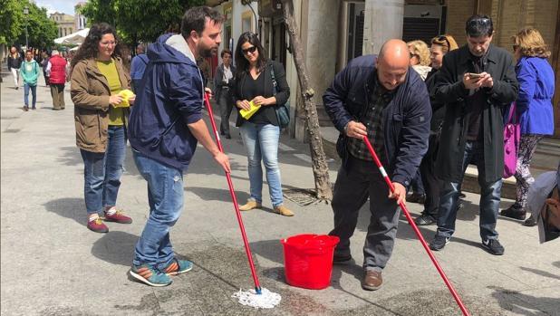 Imagen de los podemitas fregona en mano en la calle Larga de Jerez de la Frontera