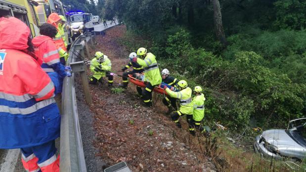 Los bomberos trasladan al herido a la ambulancia por el terraplén