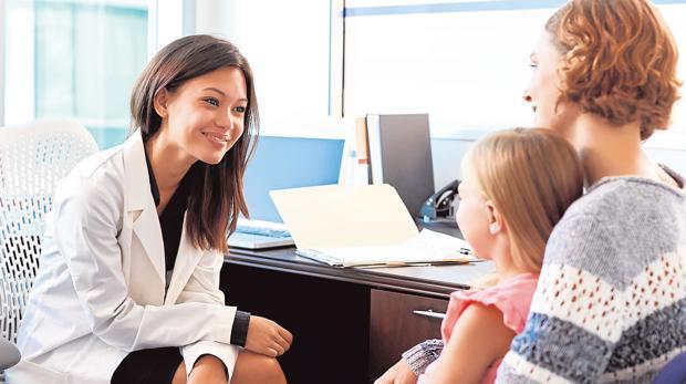 Una doctora atiende a una niña en su consulta