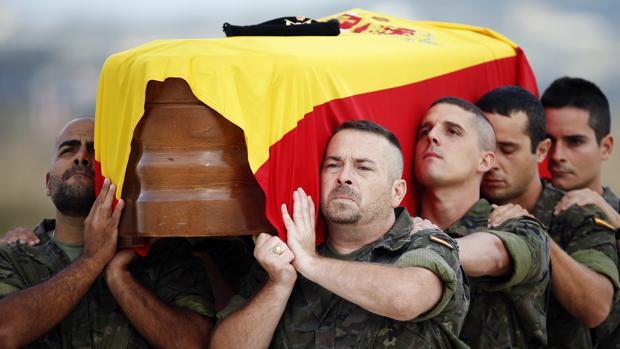 El féretro con los restos mortales de Aarón Vidal López, envuelto con la bandera nacional, es trasladado a hombros hasta el coche fúnebre a su llegada a la terminal militar del aeropuerto de Manises (Valencia)