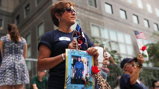 Una mujer sostiene la imagen de un policía fallecido en los atentados del 11-S en Nueva York durante una marcha en recuerdo de las víctimas