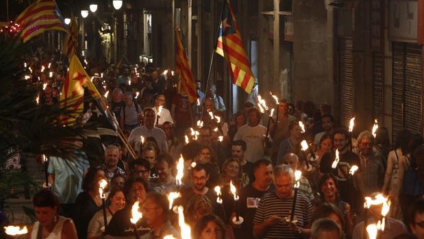 Simpatizantes de Esquerra Republicana de Catalunya se dirigen esta noche con antorchas a la Fossar de les Moreres, en Barcelona, para participar en la Vigilia de la Diada organizada por ERC-Barcelona Vella