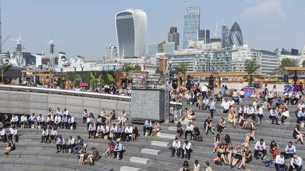 Los londinenses disfrutan del sol en la hora del almuerzo, en la City, ayer