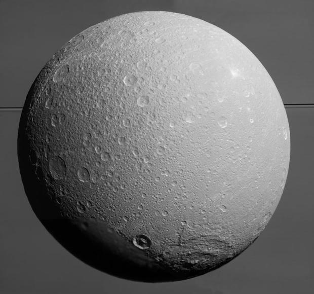 Dione con Saturno y sus anillos en el fondo