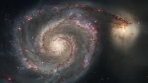 La galaxia Remolino (a la izquierda) se está fundiendo con la pequeña galaxia NGC 5195