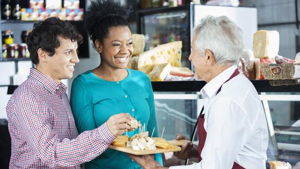Unos jóvenes degustan unas muestras gratuitas en un supermercado
