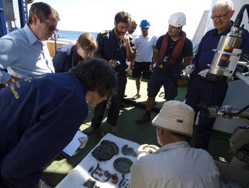 El equipo de arqueólogos y los observadores del IEO y la Armada, ante las piezas recuperadas