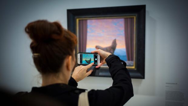 Una mujer fotografía uno de los cuadros de Magritte incluidos en la exposición