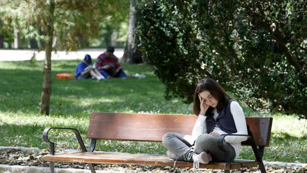 Una niña lee un libro sentada en un banco