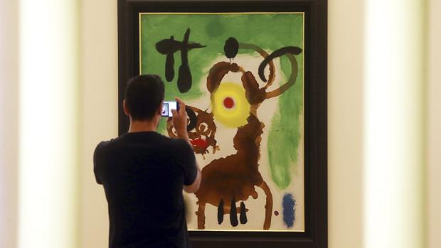 Un visitantefotografía un cuadro en la exposición «Joan Miró: Materialidad y Metamorfósis», en Oporto