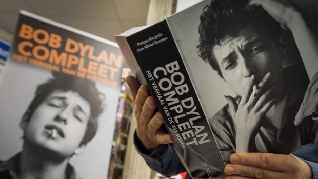 Una hombre lee un libro de las letras de Bob Dylan ayer en Rotterdam