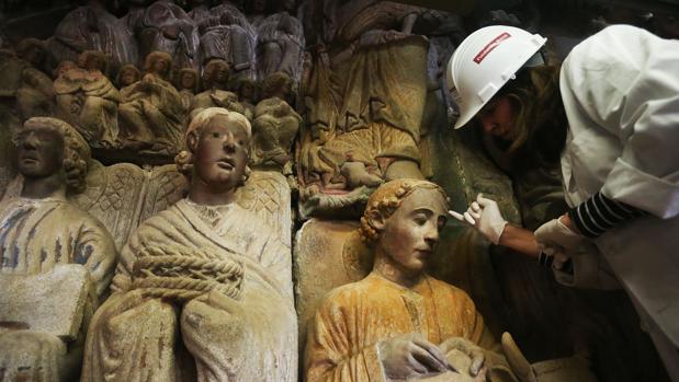 Una restauradora coloca un nanogel en la frente del evangelista san Lucas para retirar suciedad