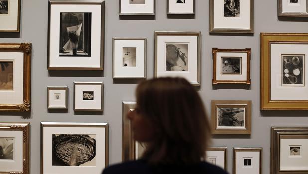 Una mujer delante de varias de las fotografías de la colección de Elton John