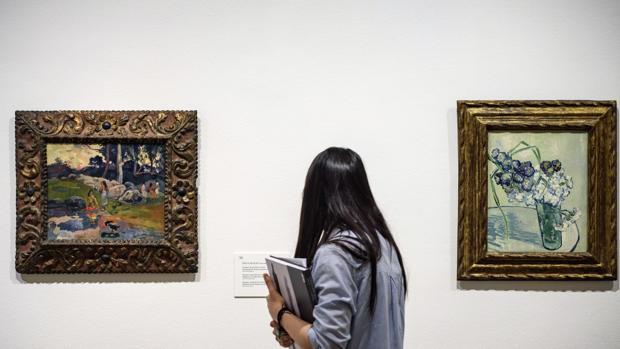 Una mujer observa 'Mujeres a la orilla del rio' de Gauguin (i) y 'Naturaleza muerta, jarrón con claveles' de van Gogh