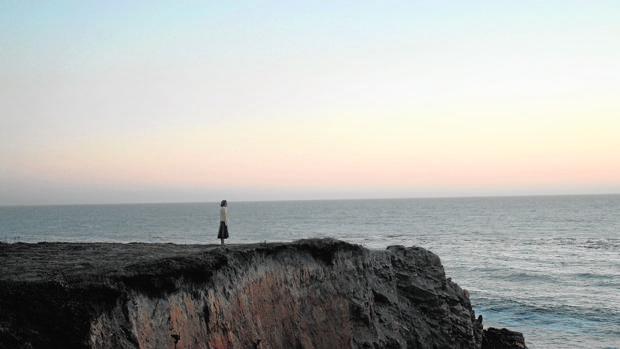 Una joven contempla el océano en un acantilado en California