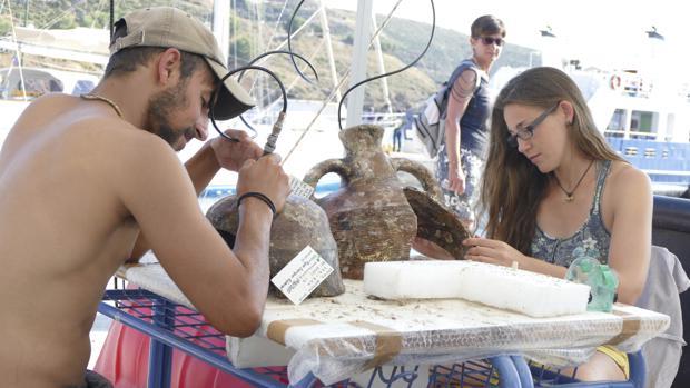 Unos arqueólogos limpian objetos extraídos de uno de los hallazgos del archipiélago de Furni, en el mar Egeo oriental