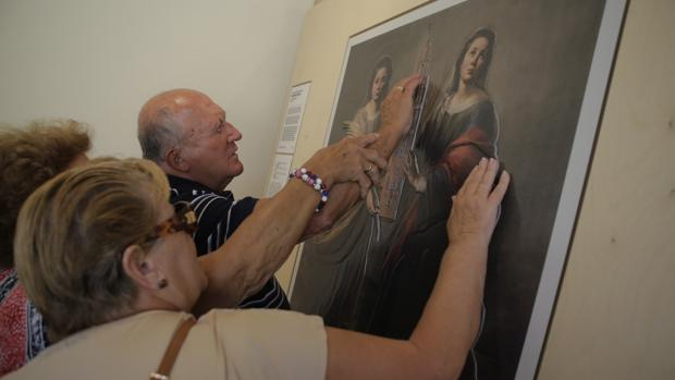 Los invidentes Jesús Casanueva y María Joséfa Mogrera tocando el «murillo» de la exposición