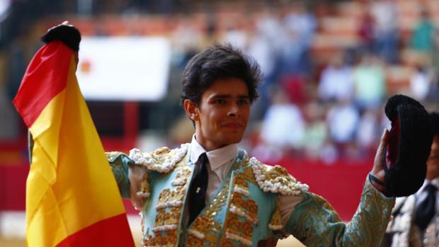Juanito pasea la oreja con la bandera de España