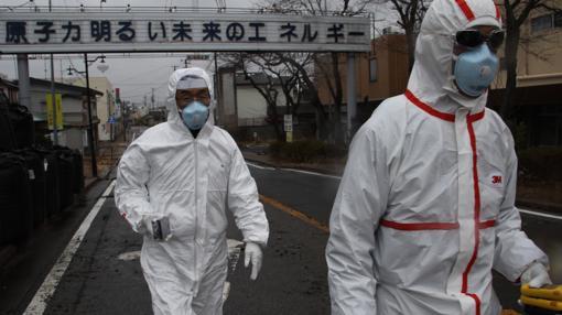 Midiendo la radiación en Futaba, uno de los pueblos evacuados alrededor de la central de Fukushima 1. «La energía nuclear es el motor de nuestro brillante futuro», reza el letrero del fondo.