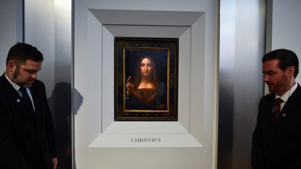 Dos miembros de seguridad, junto a «Salvator Mundi», de Leonardo da Vinci, en la sala Christie's de Nueva York