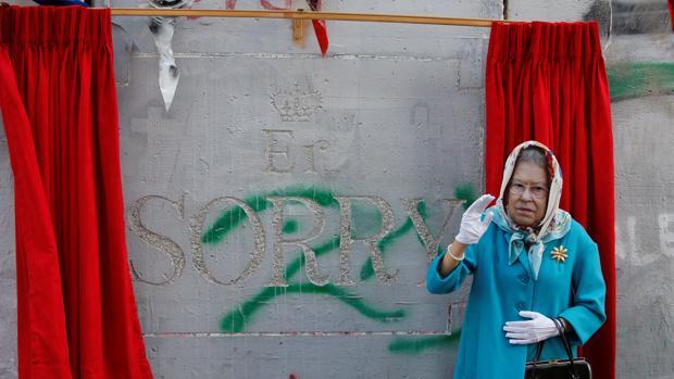 Un individuo disfrazado de la reina Isabel II gesticula con la obra de Banksy detrás