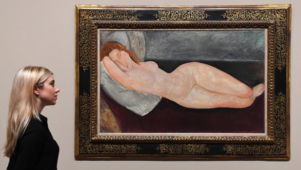 Una mujer posa junto a uno de los desnudos presentes en la exposición de Modigliani en la Tate Modern