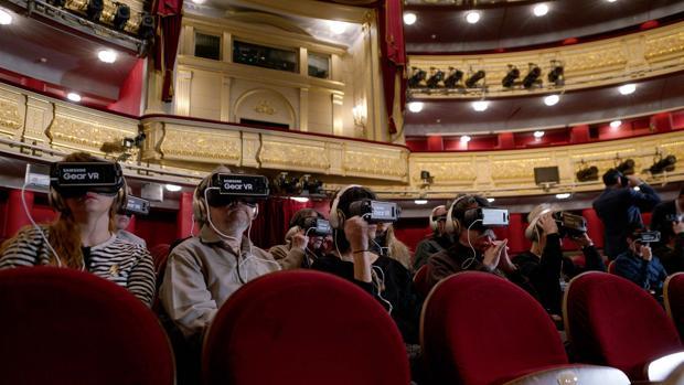 Varias personas, con las gafas de realidad virtual, en el patio de butacas del Teatro Real