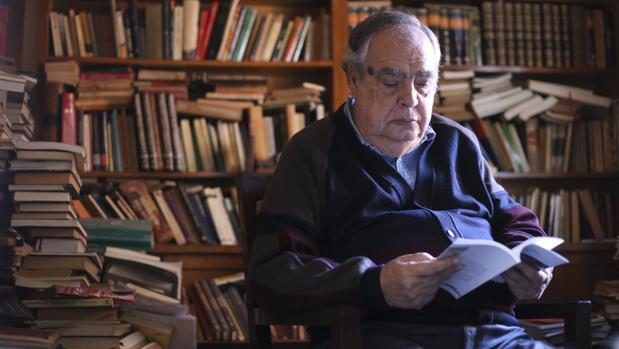 Julio Manuel de la Rosa en su estudio leyendo un ejemplar de su ultima novela