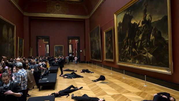 Los activistas, tirados en el suelo junto a «La balsa de la medusa» en una sala del Louvre