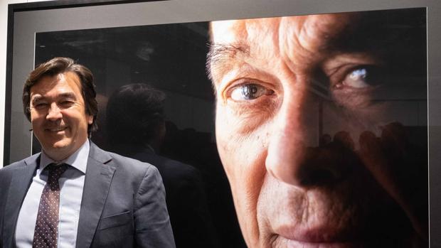 El fotógrafo Tomás Muruaga, en la exposición «Sol y sombra» junto a un retrato de Curro Romero