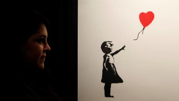 Una joven contempla «Niña con globo», una de las imágenes más icónicas de Banksy