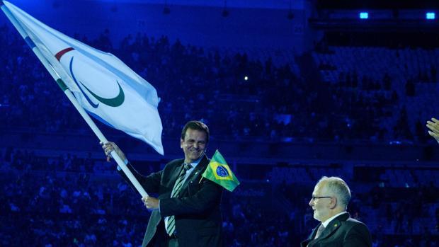 El alcalde de Río de Janeiro, Eduardo Paes, sujeta la bandera olímpica durante la ceremonia
