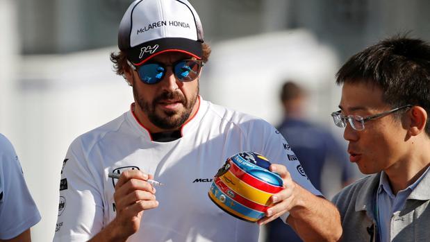 Fernando Alonso firma una réplica de un casco en Suzuka