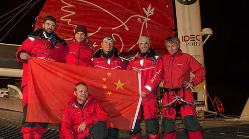 """La tripulación del """"IDEC Sport"""" luciendo la bandera China en recuerdo al desparecido Guo Chuan"""