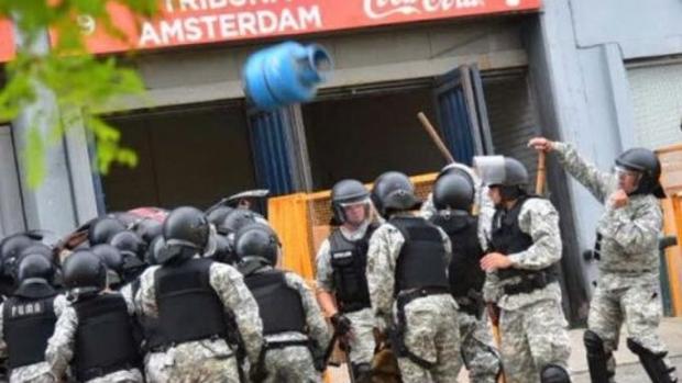 La garrafa en el momento en que cae arrojada desde una tribuna contra la policía que estaba en el exterior