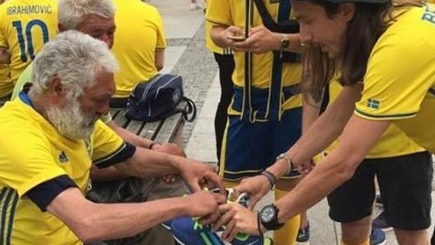 Los aficionados entregan las zapatillas al mendigo