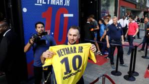 Un aficionado del PSG muestra una camiseta de Neymar recientemente adquirida tras soportar una larga cola