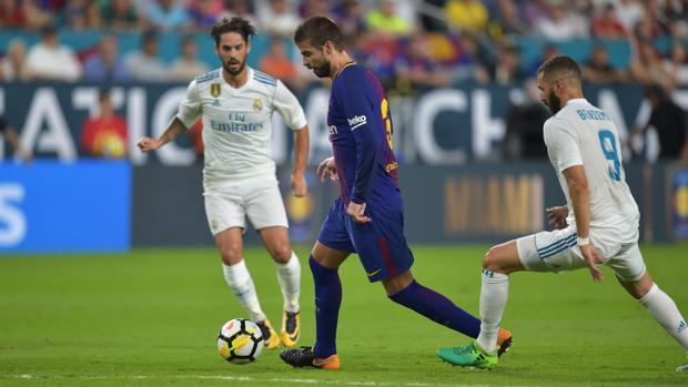 Isco y Benzema tratan de quitarle la pelota a Piqué