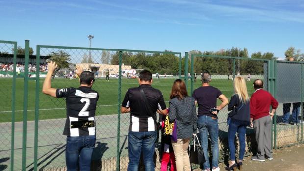 Aficionados del Cartagena viendo el partido ante el Granada B detrás de una valla