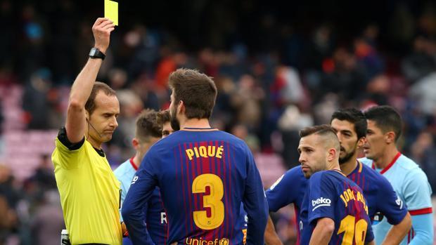 Gerard Piqué ve la tarjeta amarilla tras el pitido final del partido