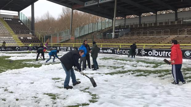 Aficionados del Burgos en El Plantío retirando la nieve este domingo