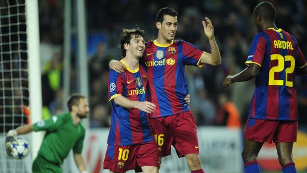 Eric Abidal, Sergio Busquets y Leo Messi durante un partido