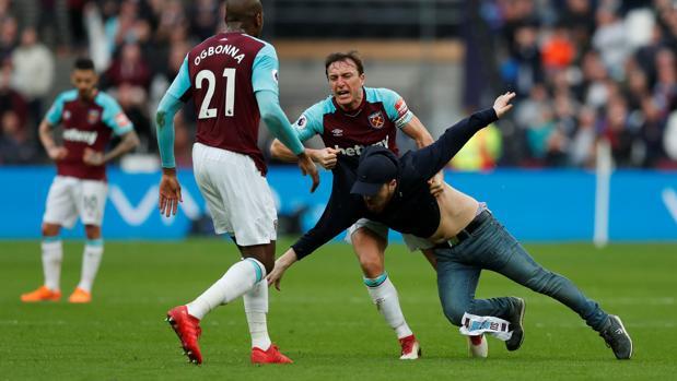 Mark Noble, jugador del West Ham, se enfrenta a uno de los aficionados que han saltado al césped